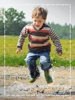 Springendes Kind mit Gummistiefeln in Mitten einer Wasserpfütze - freut sich auf den Geburtstag