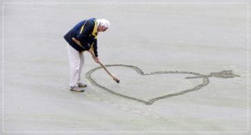 Ein alter Mann mahlt für seine Mutter ein großes Herz in den Sand
