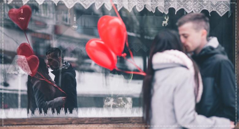 Ein sich küssendes Paar mit Herzluftballons